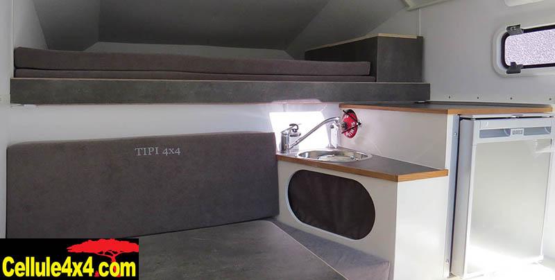 Un évier, un frigo et des rangements à proximité du lit en position basse