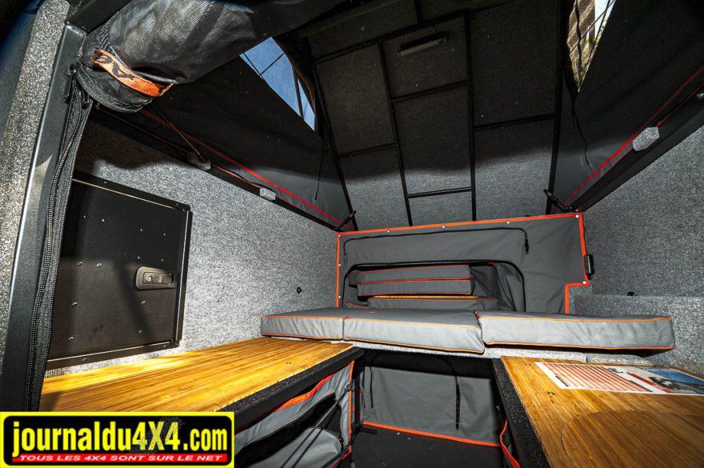 Des banquesttes de part et d'autre de la cellule, dessous des rangements, les coussins servent pour le lit bas, et enfin un accès vers le coffre cuisine (à gauche)