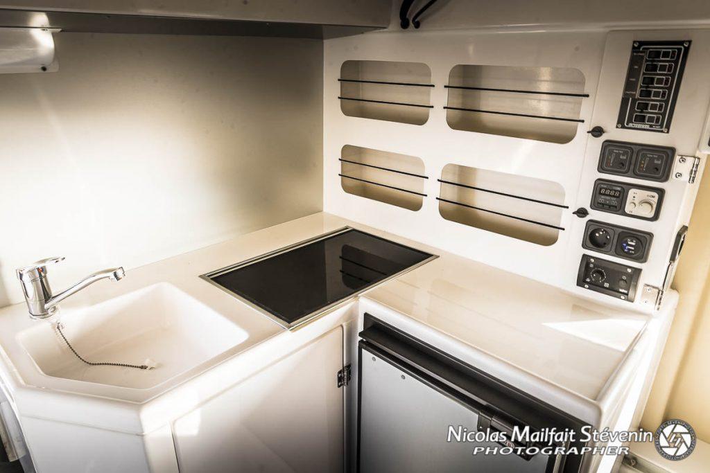 le coin cuisine de la cellule Azalaï avec évier, plaque de cuisson, rangements et frigo