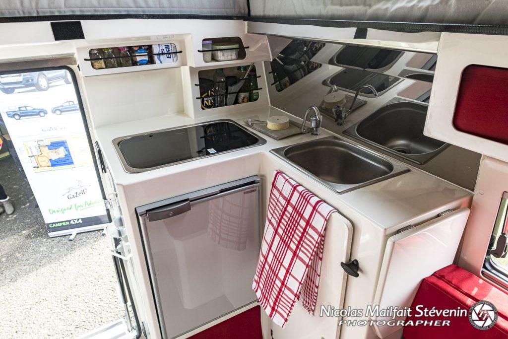 La cuisine est vraiment pratique, avec un évier de grande taille pour une cellule et une plaque à deux foyers sous laquelle se trouve le frigo. On dispose aussi sur le côté droit d'un placard, d'une tablette rabattable qui servira de plan de travail et de divers rangements près de la zone cuisson