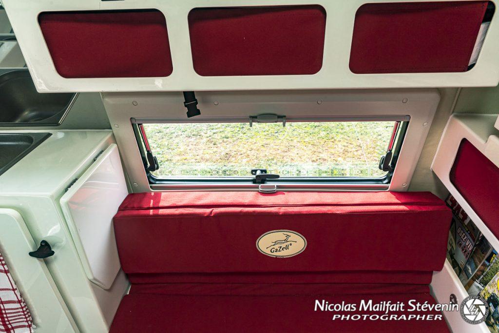 Les fenêtres sont dotées d'occultants et de moustiquaires, vous avez des rangements au dessus des banquettes et des coffres en dessous et des rangements sur le côté. On voit la tablette qui peut se relever pour servir de plan de travail