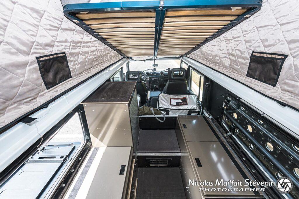 Une vue de l'intérieur du Defender 130 avec son aménagement et le lit en position haute