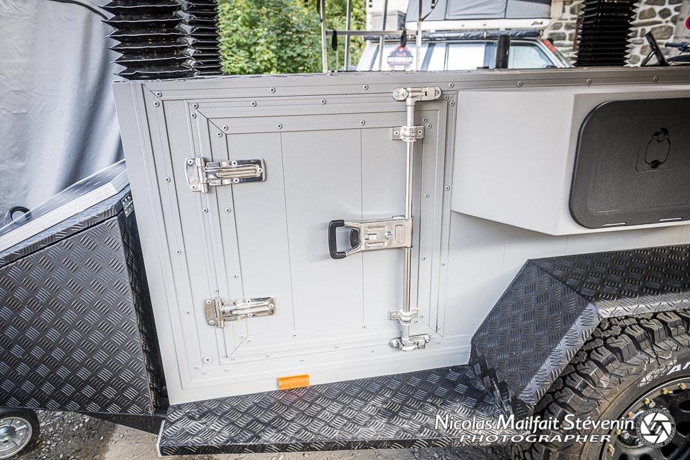 la porte pour le rangement du frigo est sur l'avant gauche