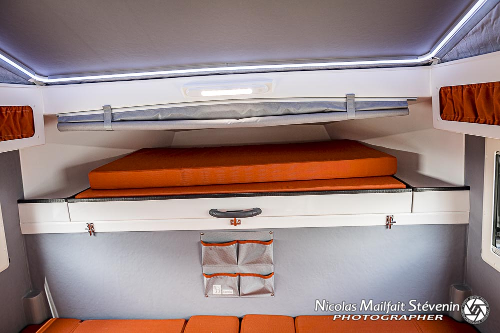 le grand lit de 140x200 en position fermé, juste au dessus on aperçoit le petit rideau qui permet de fermer la capucine quand on roule