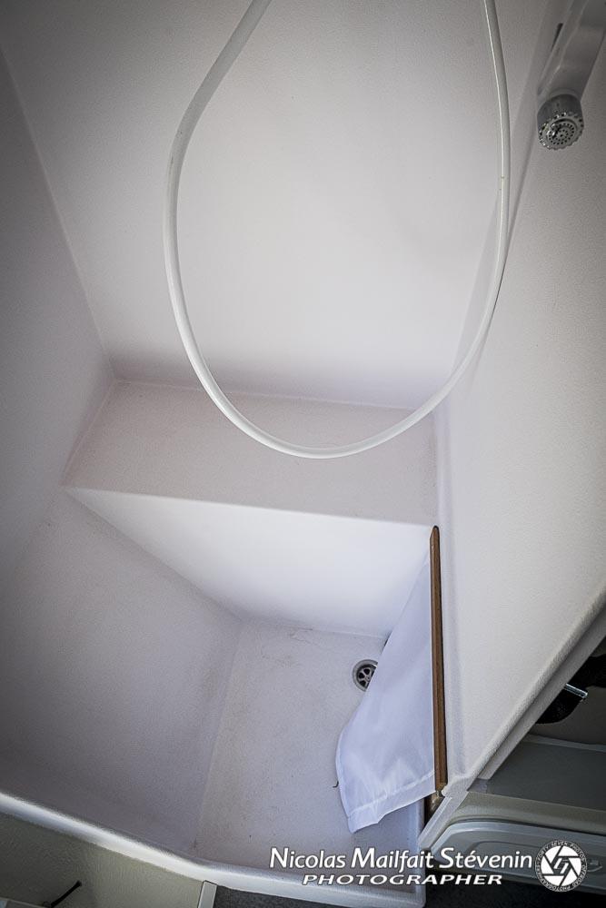 le bac de douche et le rideau qui protèges le rangement des toilettes sèche