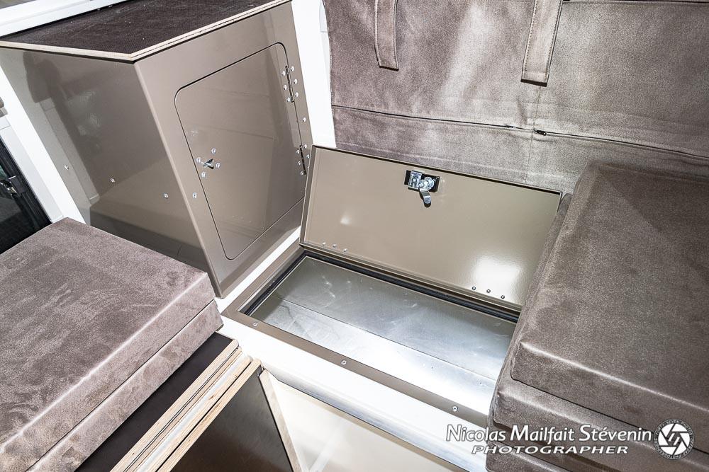 le meuble de rangement situé derrière la benne et un coffre de rangement sous une banquette